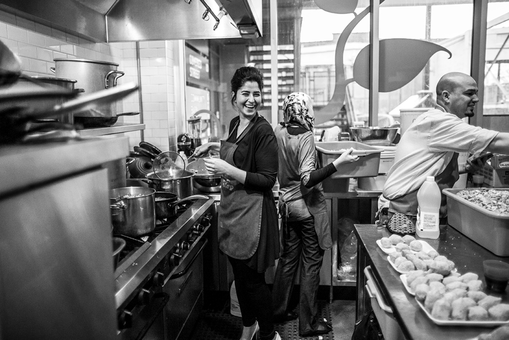 """Diala Aleid stands in the kitchen helping chef Rabi Abo Al Zahab prepare Fatteh, a traditional dish that includes fried pita bread, tahini and chickpeas topped with garnishes such as pomegranate seeds, beets and parsley for the 'Supper With Syria' fundraiser for Syrian refugee families on Nov. 29, 2015. Aleid was born in Damascus, raised in the United Arab Emirates and came to Canada a year and a half ago, and hopes to do whatever she can to help Syrian refugees. """"We all have this heartbreak,"""" she said. """"But it's been so nice to work together with Syrians and Canadians. We've been singing our songs and teaching our language."""" 
