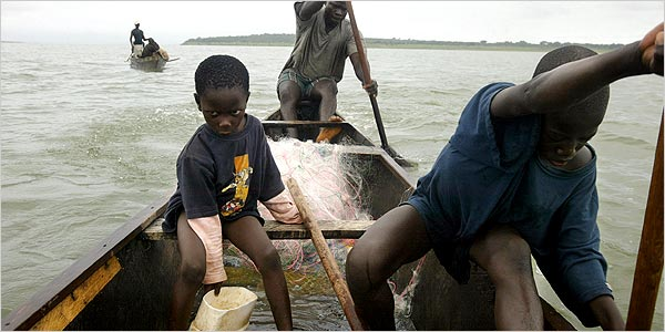 On Lake Volta in Ghana, Mark Kwadwo, 6, left, scoops water in the canoe of Kwadwo Takyi, rear. Kwabena Botwe, 11, paddles. Photo Credit: Joao Silva for The New York Times