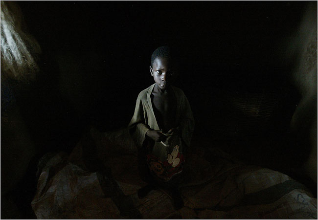 "Mark Kwadwo, 6, in the small dark room, where he sleeps on the dirt floor and rises before dawn to work on Lake Volta, a two-day trek from his family home. ""I don't like it here,"" he whispered to a visitor, out of earshot of his employer. Photo Credit: Joao Silva for The New York Times"