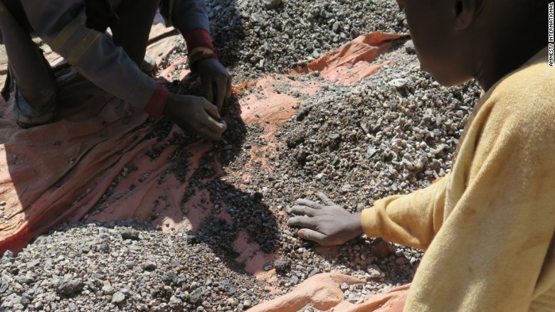 Photo of a 13-year-old named Charles sorting through by-products of industrial mines to find rocks containing cobalt. (CNN)