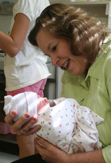 Photo of Mike's wife holding their newborn granddaughter at the hospital.