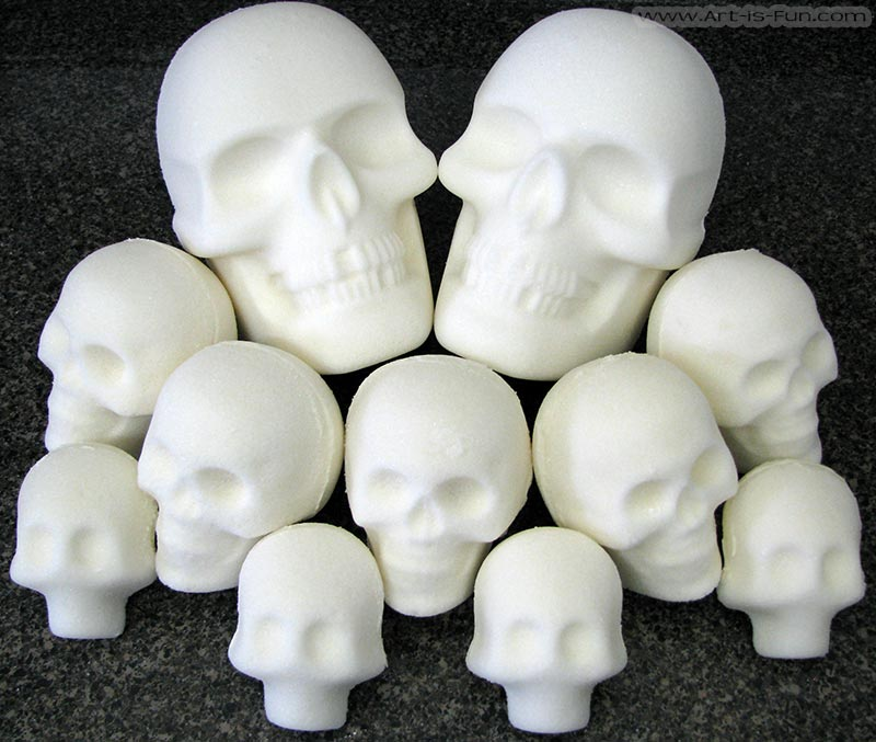 Two life-size skulls surrounded by medium and large sugar skulls.