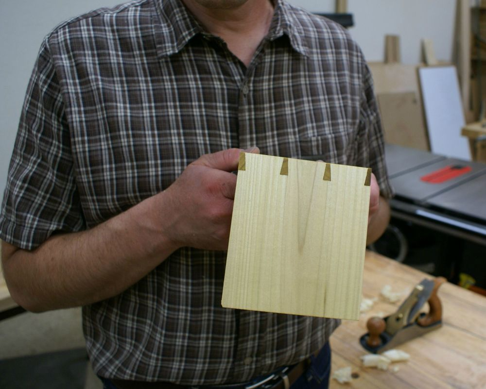 A student with their first dovetail joint. This joint is made primarily with a specialized saw called a dovetail saw. It consists of two pieces of wood, a tail board and a pin board, joined together.