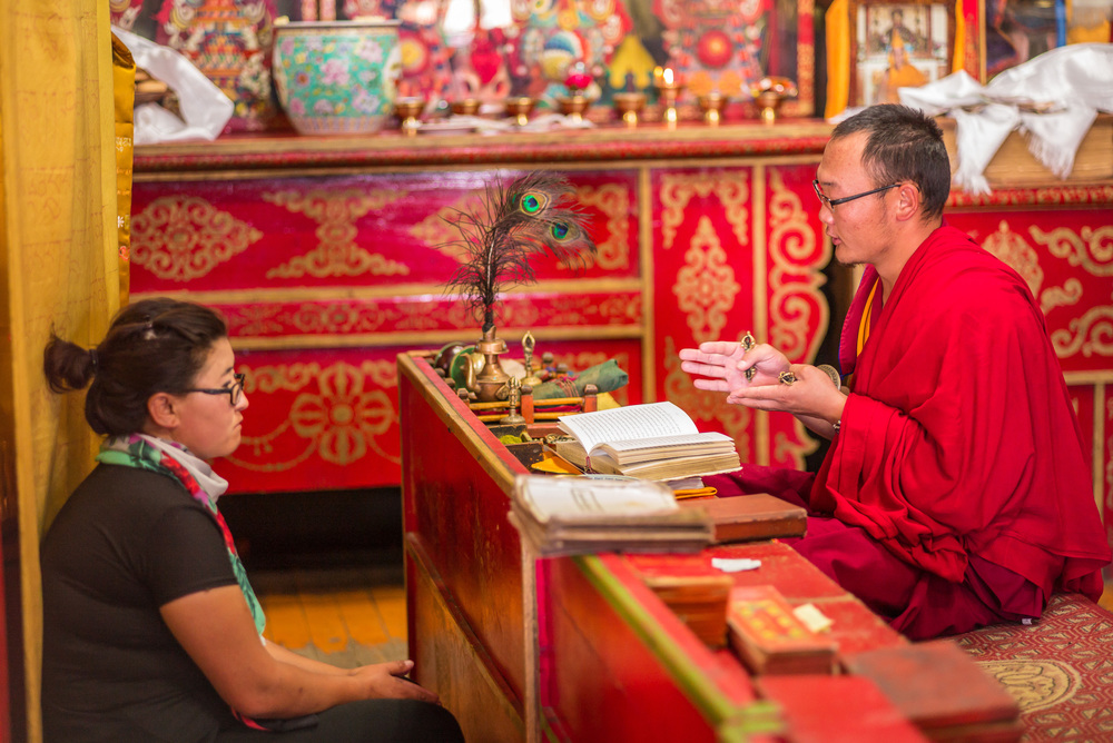 Buddhist supplicant and Monk during prayers and chanting