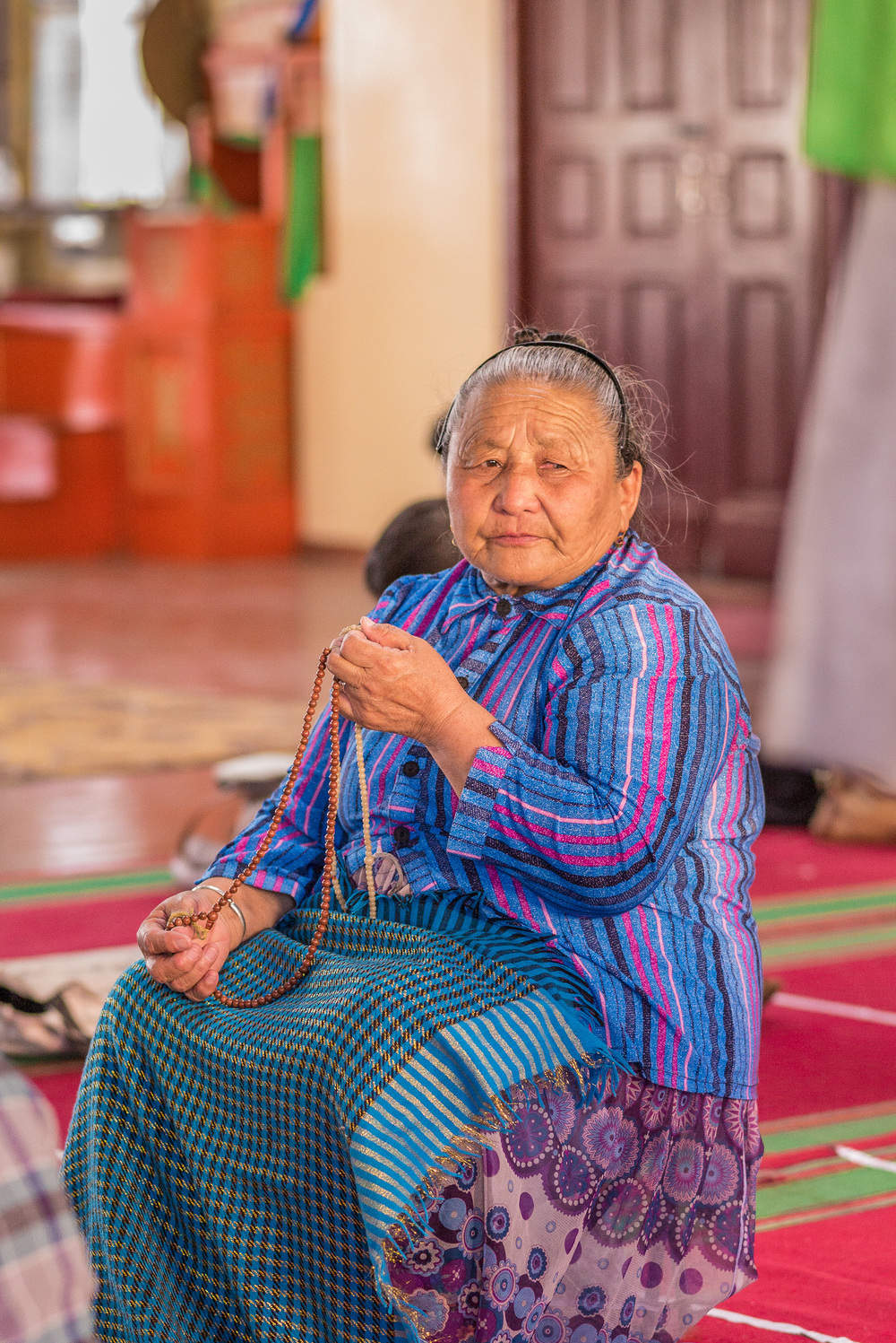 Mongolian supplicant chanting mantras and counting them on her mala