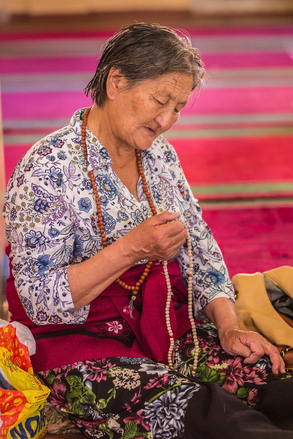 Elderly Mongolian worshipper counting prayers on her mala