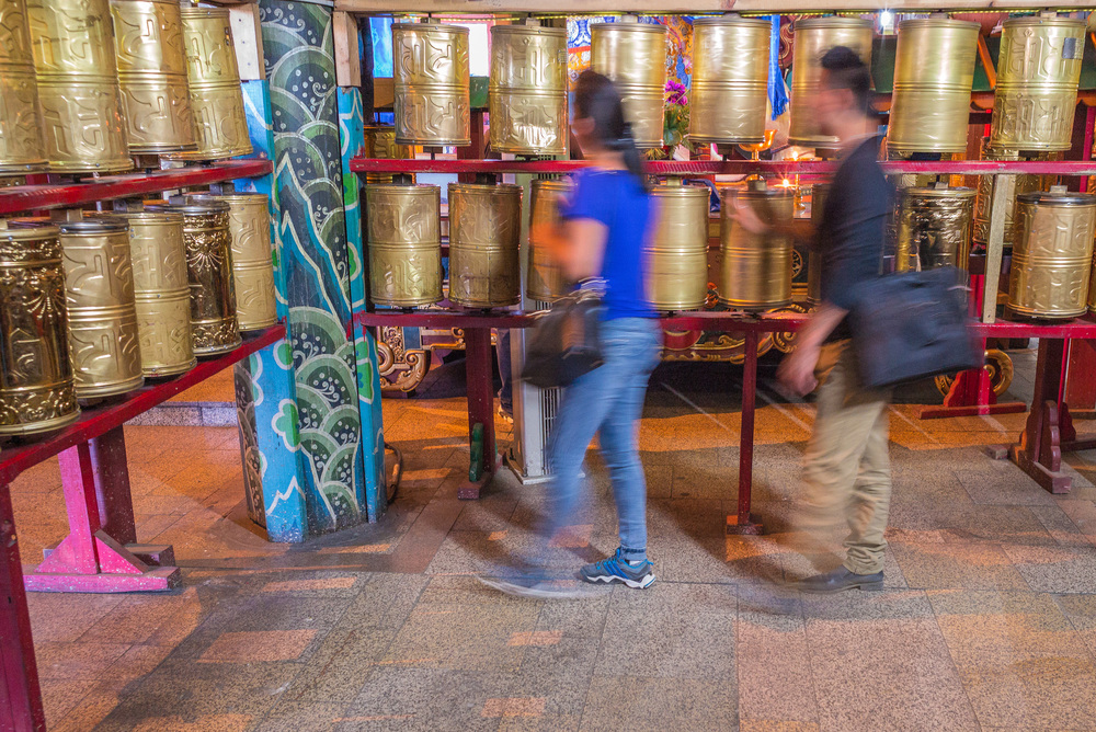 Worshippers spin prayer wheels in main temple