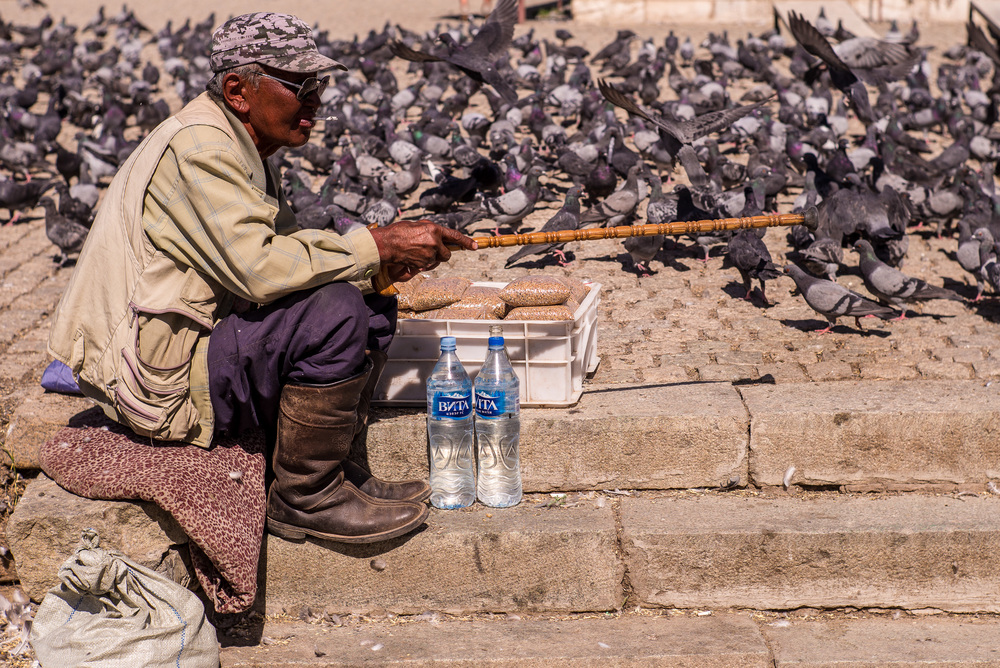Mongolian man selling bird food to monastery visitors