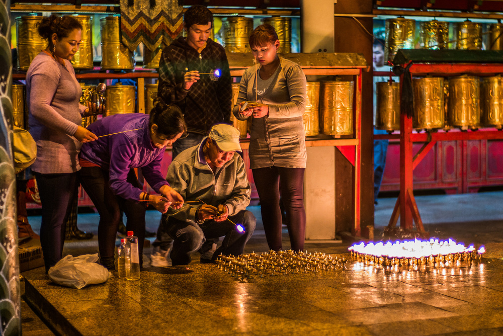 Mongolian family lighting candles at the base of Avalokiteśvara statue, main temple