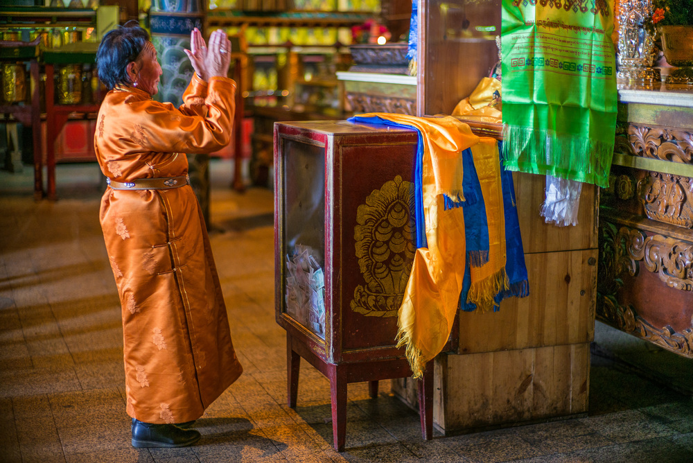 Mongolian lady offers prayers to a Buddha statue