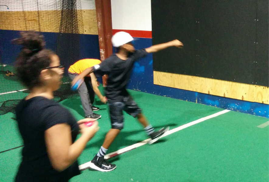 Youth baseball player performs a recovery day roll-in throw USING a driveline baseball blue (450g) plyo care ball