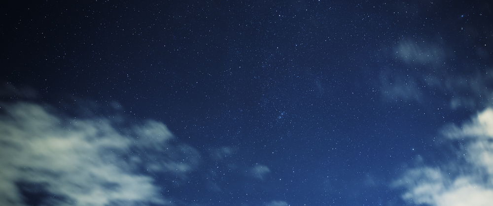 Rapidly moving stratus clouds reveal the Orion constellation during the night.