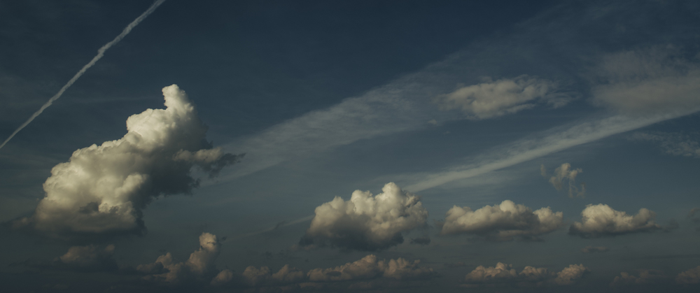 Patches of cumulus clouds along cirrostratus fibratus in the upper atmosphere.