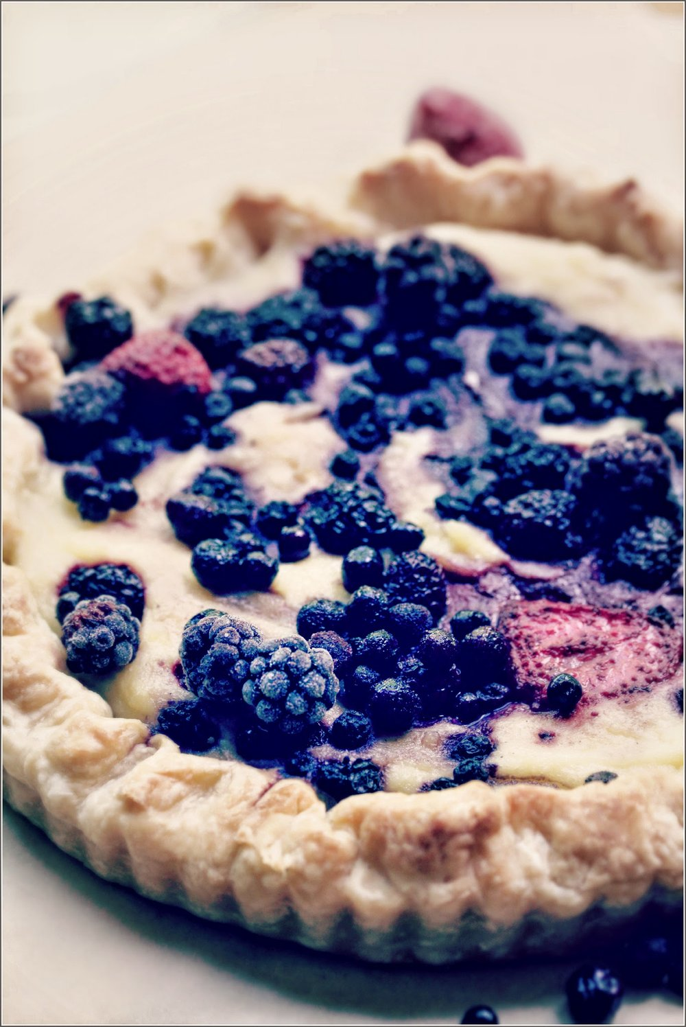 Mixed Berry Tart - 2 9-inch tarts, about 16 ServingsIngredients:For the pastry shell:2 ½ cups all-purpose flour1 tablespoon granulated sugar¾ teaspoon salt½ cup salted butter, chilled and cut into small pieces½ cup vegetable shortening, chilled and cut into small pieces6 tablespoons buttermilk, chilledFor the filling:⅓ cup heavy cream1 ½ cup whole milk5 tablespoons granulated sugar1 teaspoon pure vanilla extract⅓ cup semolina1 large egg1 ⅔ cups assorted fresh berries, stems removed, rinsed and sliced as neededFor serving:Confectioners' sugar, for dusting2-3 cups assorted fresh berries, stems removed, rinsed and sliced as neededHandful rinsed fresh mint leaves, optionalInstructions:To prepare the tart dough and pre-bake the pastry shell:In a large bowl, combine the flour, sugar, and salt. Add the butter and vegetable shortening. Cut them in using your hands or a pastry blender. Blend it till the mixture resembles a coarse meal the size of peas.Add the buttermilk and mix it until the mixture is just moistened. You don't want it wet.Press the dough together and divide it in half. Wrap each piece in clear film and chill it for at least one hour, up to 24 hours.Prepare 2 9-inch tart pans with removable bottoms by lining the outside with aluminum foil. (This will prevent spillage if  while the tart is baking.Remove one piece of pastry dough from the refrigerator. Remove the plastic film. Lightly dust a clean work surface with flour and roll the dough out until it a circle large enough to cover one tart pan and most of the sides comfortably. Carefully line the pan with the pastry dough and trim the edges. Repeat this with the second piece of pastry dough. Refrigerate both for at least one hour, up t 24 hours.Preheat oven to 325 degrees F. Cut out two pieces of parchment paper or foil  large enough to cover the base and sides of the tart pans.  Place them inside the pastry shells and fill with dried beans or rice so the sides of the pastry are totally supported by the beans and won' collapse during baking. Blind bake the shell for 20 to 25 minutes, until it is very  light brown. Remove from the oven and take out the beans or rice. Allow to cool while you prepare the filling. Leave the oven on.To make the filling, put the butter, cream, milk and sugar in a clean saucepan. Place the pan on the stove and bring to a boil. Let it simmer while you whisk in the semolina in a slow stream. Continue whisking until the mix comes back to a boil and thickens up like porridge. Remove from the heat and whisk in the vanilla and the egg.Pour the semolina mixture into the pastry shells  and level them with a wet spatula. Divide the prepared berries evenly between each tart and push them gently into the semolina mixture. Place in oven and bake until the filling is slightly golden, 20 to 25 minutes.Remove the tarts from the oven and allow to cool completely before removing them from the pans.When ready to serve, dust the tarts with confectioners' sugar. Slice into wedges and serve garnished with more fresh berries. Add a few fresh mint leaves, if you like.Enjoy.Notes:This recipe was adapted from Tate's Bake Shop Cookbook by Kathleen King (for the pastry dough) and Ottolenghi: The Cookbook by Yotam Ottolenghi and Sami Tamimi for the semolina and berry filling.