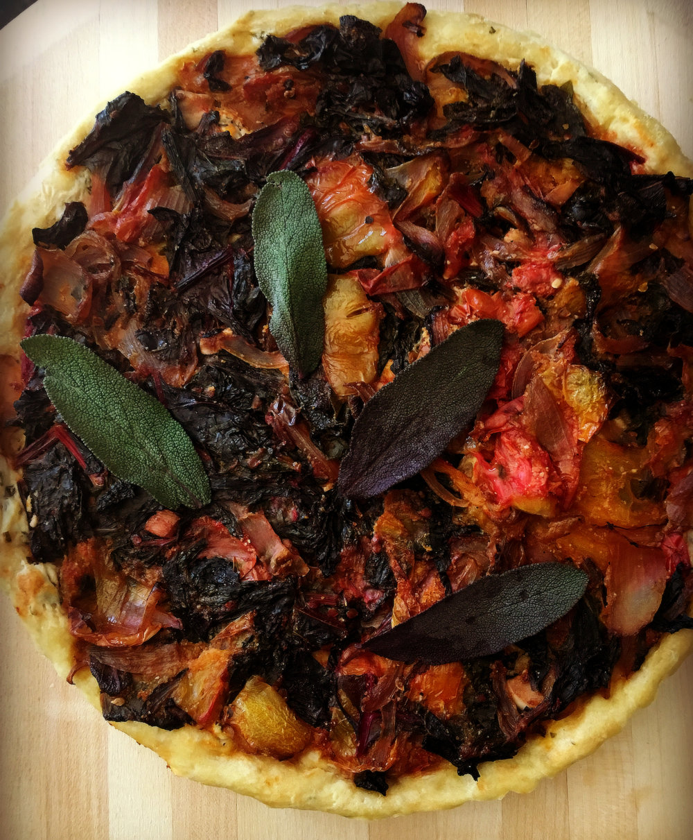 Tomato & Chard tart  - Yield: One ten-inch tart, about 8 servingsIngredients:For the yeasted dough:2 ¼ teaspoons active dry yeast½ teaspoon sugar⅔ teaspoon salt½ cup water3 tablespoons olive oil1 egg, lightly beaten1 cup bread flour¾ cup whole wheat flour2 teaspoons dried  Italian herb blend (oregano, thyme, marjoram, & sage)For the tart filling:2 tablespoons olive oil2 small onions or shallots, thinly sliced2 cloves garlic, minced finely1 ½ pounds heirloom or other fresh tomatoes, peeled, seeded, & chopped2 cups Swiss chard, rinsed, stems removed, & cut into thin strips2 tablespoons chopped fresh sage, plus a handful more for serving¼ cup cornmeal or polentaSalt and freshly ground black pepper½ cup herbed cream cheese or goat cheeseInstructions:To make the yeasted dough, dissolve the yeast and sugar in the water and let stand until it's bubbly, about ten minutes. Whisk the oil, egg, and salt together with the proofed yeast, then stir in the flours. When the dough is too stiff to work with a spoon, turn it onto a lightly floured counter and knead until smooth and elastic, about four minutes. Set though dough in an oiled bowl and turn it over to coat, cover with a towel, and let rise until double in bulk, about forty-five minutes. Set aside until ready to use.To make the filling, warm the oil  over medium heat in a wide skillet. Cook the onions until translucent, about ten minutes. Add the garlic, tomatoes, chard, and fresh sage. Toss to combine and cook until all vegetables are tender, about ten minutes more. Add the salt and pepper. Remove from heat. Let the vegetables cool for a few minutes, then pour into a colander to drain off any excess liquid. Stir in the cornmeal. Allow to cool completely.To assemble and bake, preheat oven to 400 degrees F. Roll the dough into a thin circle, and line a ten-inch *tart shell with it. Add the cream cheese or goat cheese and spread evenly. Add the cooled vegetables. Spread evenly. Bake for thirty five minutes, or until the dough is golden and the filling is bubbly.To serve, allow the tart to cool slightly then remove it from its pan. Sprinkle fresh sage leaves on top. Enjoy.Notes:This recipe is closely adapted from In My Kitchen by Deborah Madison.*If using a tart pan with a removable bottom, cover the bottom in foil before baking. This will keep any excess juices from spilling into the oven.For a full meal, serve with a green salad, a platter or smoked meats or cheeses, and a bottle of chilled wine.