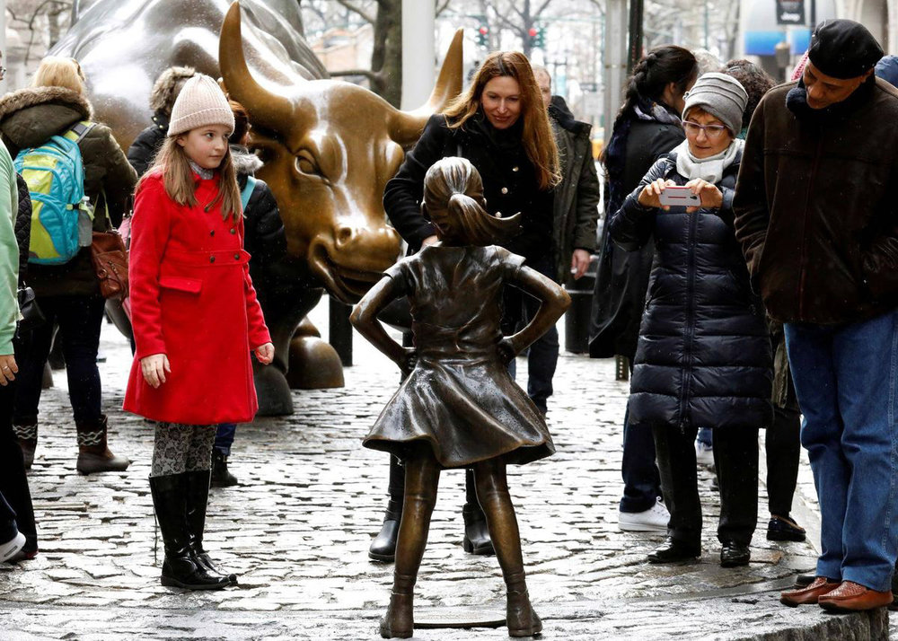 People look at a statue of a girl facing the Wall St. Bull, as part of a campaign by U.S. fund manager State Street to push companies to put women on their boards, in the financial district in New York, U.S., March 7, 2017.  BRENDAN MCDERMID/REUTERS