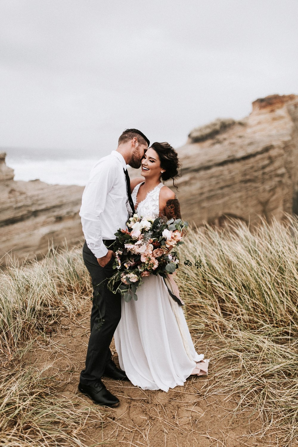newlyweds on the beach with flowers
