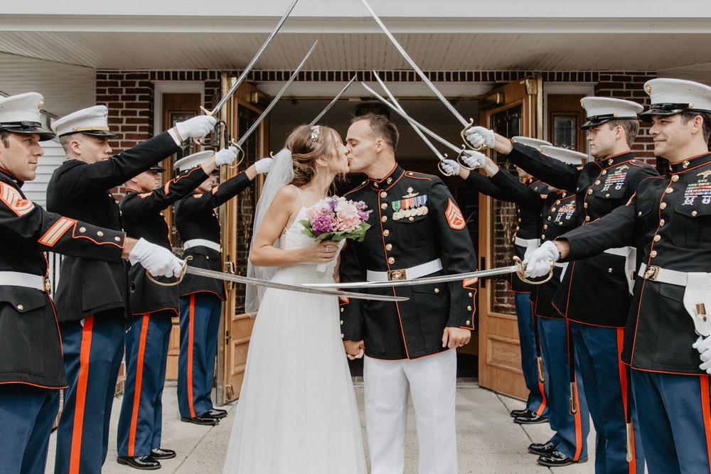 Stoneham MA bride & groom kiss beneath a sword salute outside Saint Patricks church