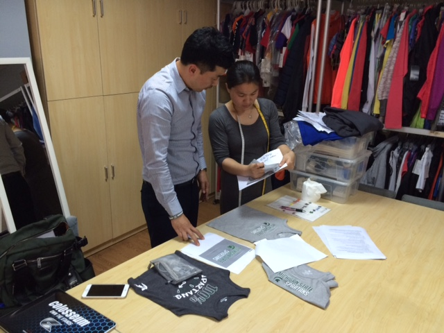 This image was taken during a 2015 Colosseum factory visit in Shanghai. They are analyzing a piece of toddler apparel, discussing width of the neckline and the accuracy of the artwork on the garment. This is a great example of one of MSU's licensees doing on-site factory visits.