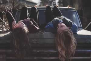 girls laying on truck hood