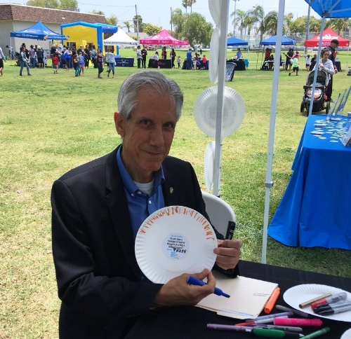 Oceanside Deputy Mayor Chuck Lowery fills out a paper plate urging state representatives to adopt anti-hunger policies.