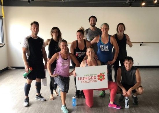 Participants in the San Diego Hunger Coalition's Work out to Fight Hunger at Ashley Lane Fitness pose to show their support after their workout.