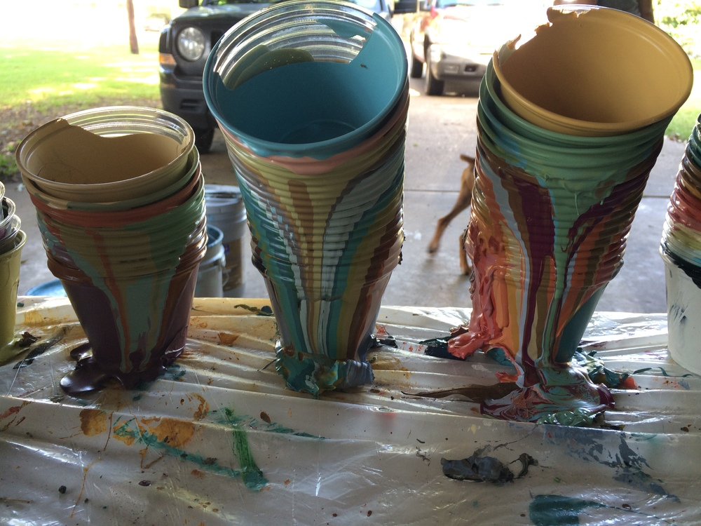We use little plastic cups to portion out the paint from the buckets into resealable containers that are much easier for us to use on site. When they are stacked up, they become awesome works of art themselves.