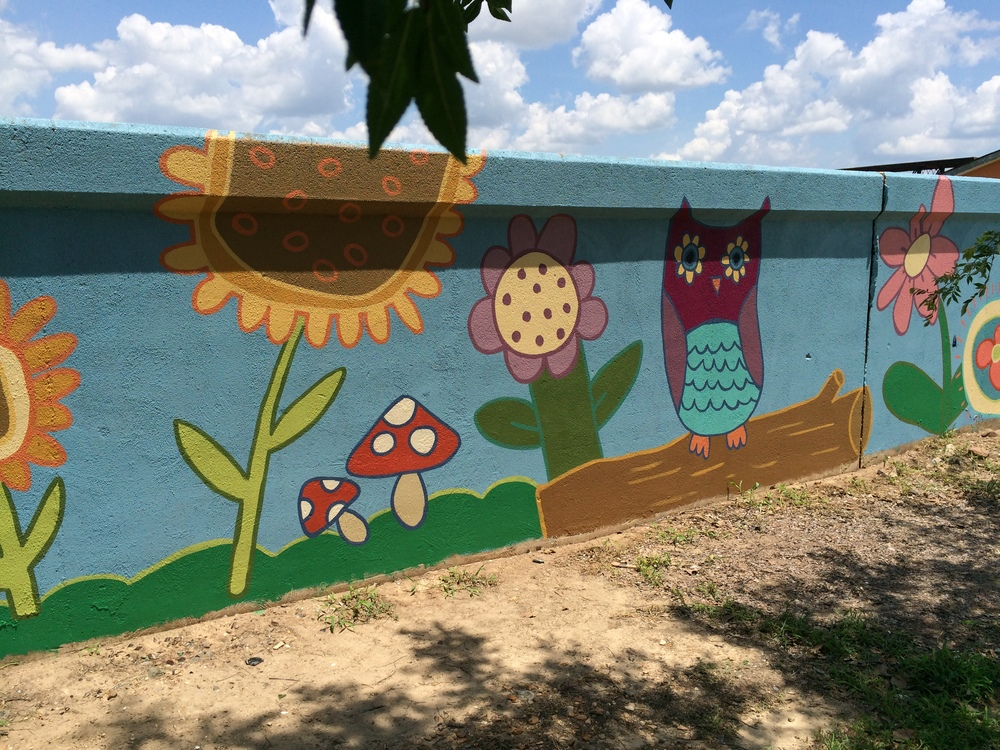 Here, you can see Katie's owl come to life amid a colorful garden. This part of the wall is behind Antique Alley on Commerce St., in front of Riverside Condominiums.