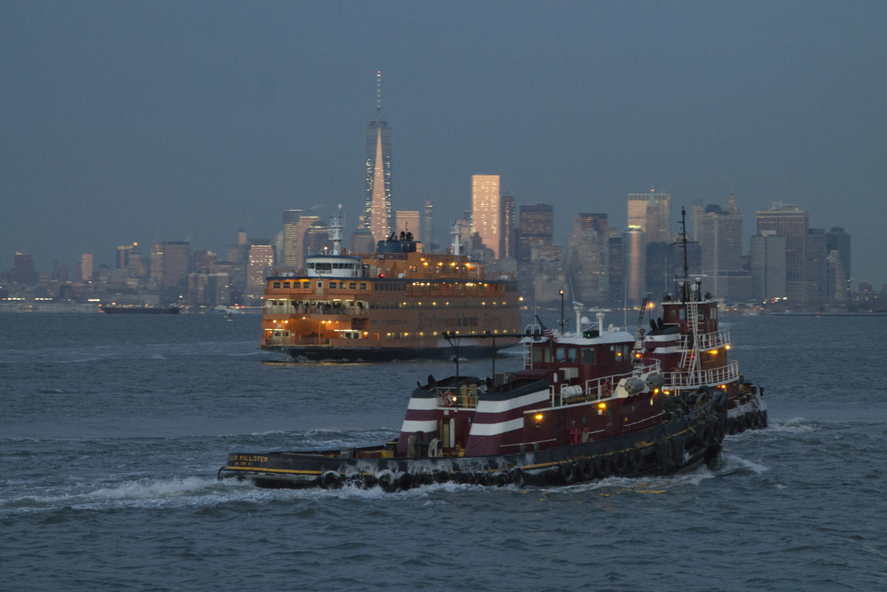 A Moran Towing company tugboat passes behind a Staten Island Ferry at dusk.