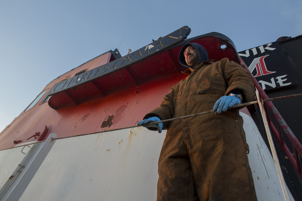 Mike Vinik stands on the edge of the  Charles Oxman   after a long day of work repairing the boat from damages it sustained during Hurricane Sandy in 2011.