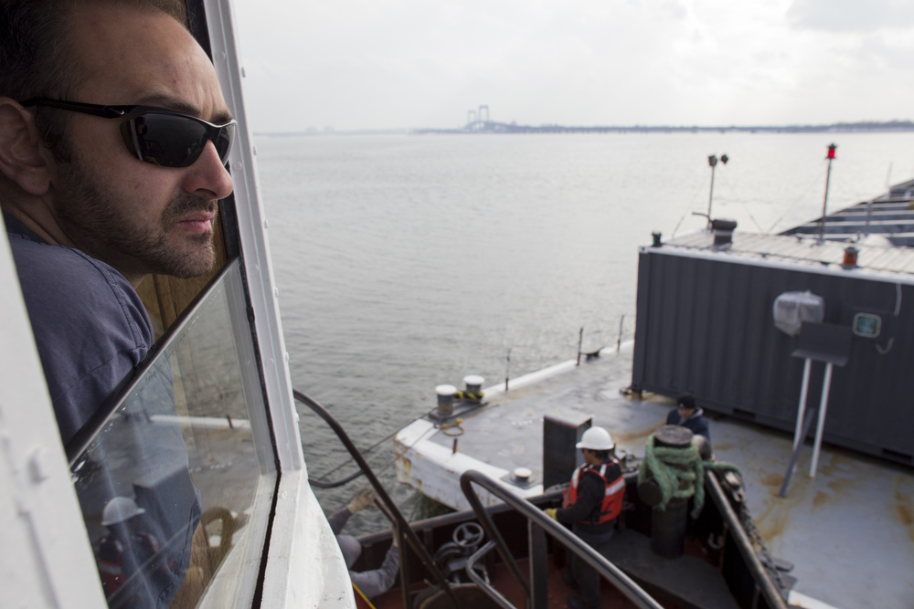 Vinik cracks the window in his tug's cockpit to get a better view of the barge's starboard side.