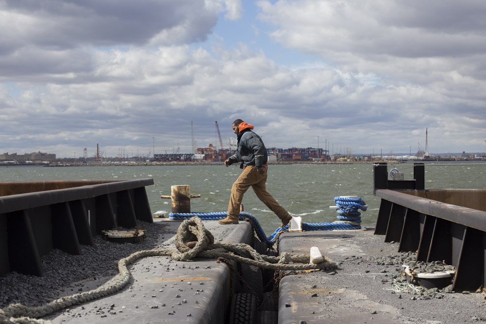 Walter Serrano, a tugboat deckhand for Brown and Sons towing, crosses between barges while moving cargo in a small inlet by Red Hook.