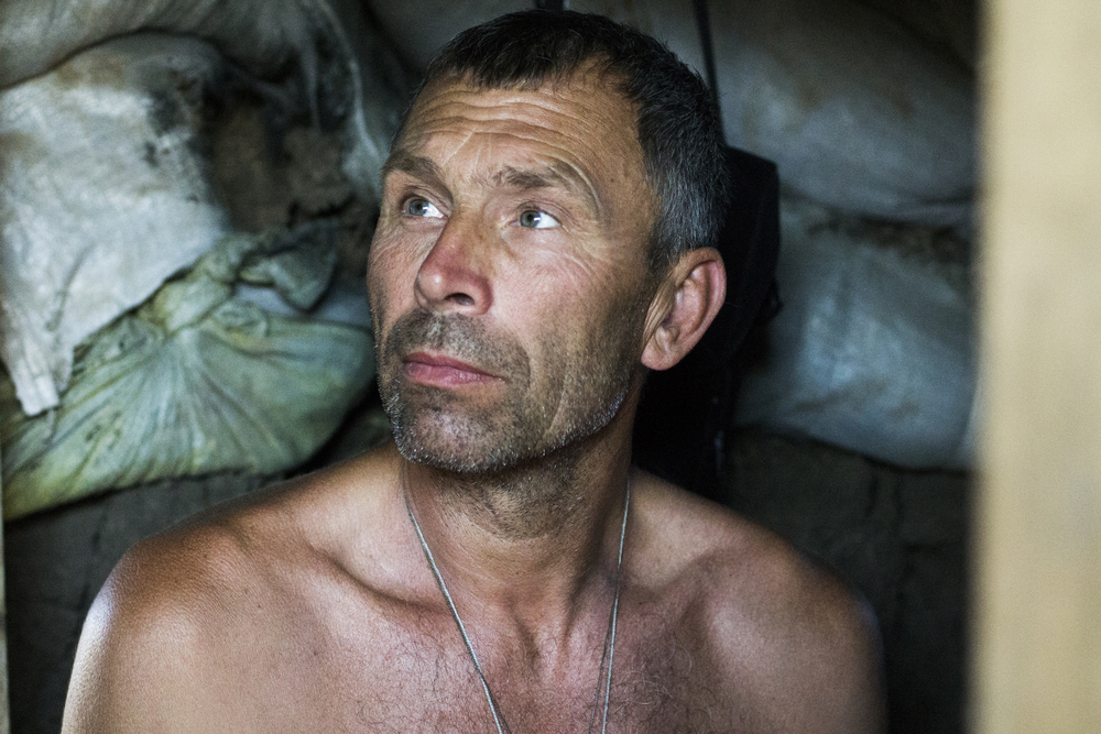 "Anatoli Ovdeechook, 52, a Ukrainian fighter known as ""Viking,"" shelters from the sun in a bunker overlooking the embattled southern city of Shyrokyne, Ukraine in July, 2015."