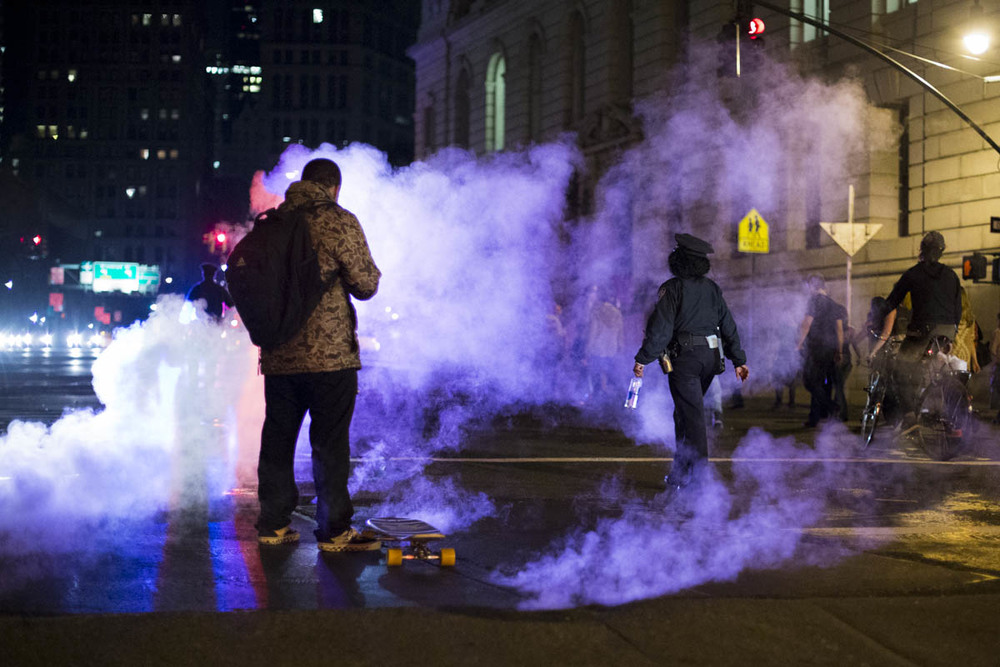 A protestor checks his phone next to steaming manhole covers in lower Manhattan on the first night of protests against a Missouri grand jury's decision not to indict the police officer who shot Mike Brown, an unarmed 18-year-old in Ferguson, Missouri. November 2014.