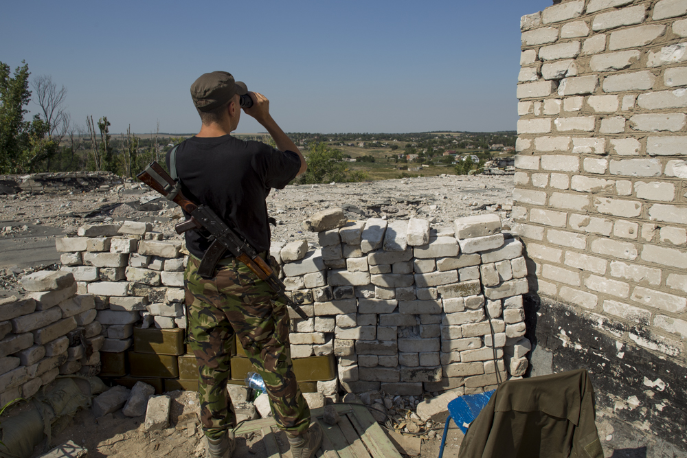 A Donbas Battalion Soldier looks out at Rebel positions from an outpost on the front line in Shryokyne, near Mariupol, Ukraine. ©Jack Crosbie, 2015.