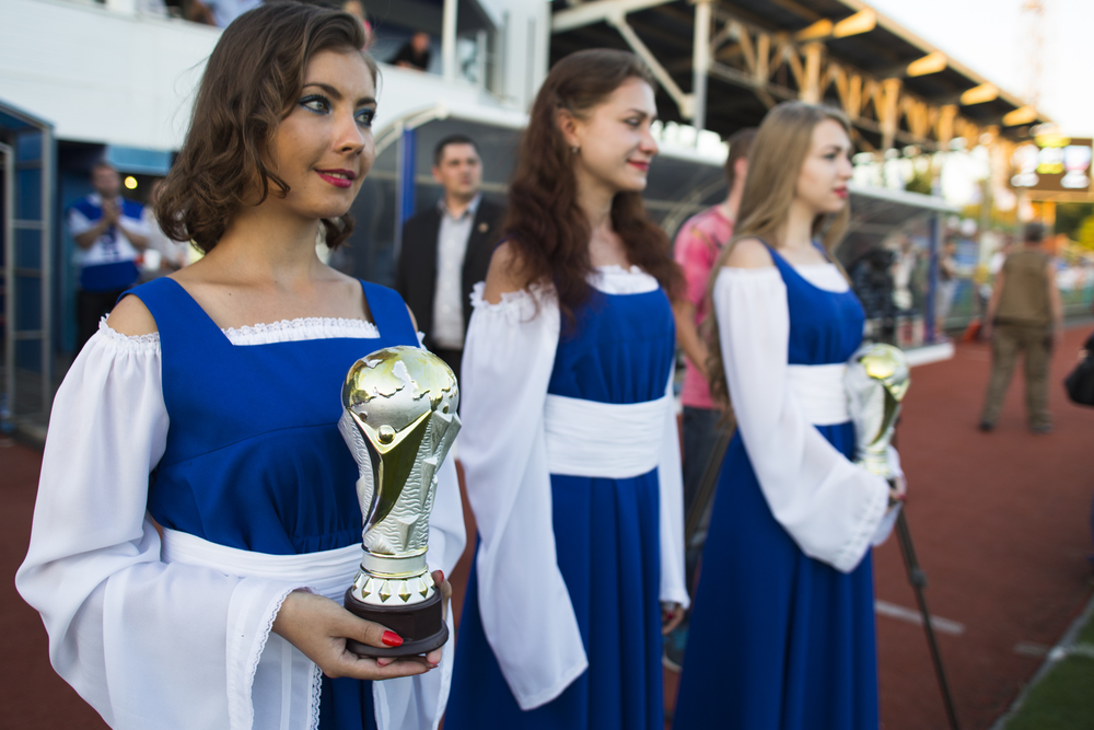 Women hand out trophies modeled after the World Cup to the Donetsk and Luhansk national teams after the first friendly competition between the two Russian-backed separatist republics. ©Jack Crosbie, 2015.