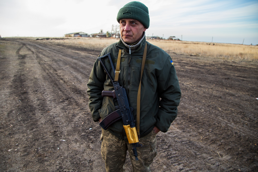 A Ukrainian BTR (light armored vehicle) driver stands with his gold-painted AKS-74U on the front line near Pisky, Ukraine.