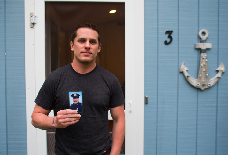 Chris Budney holds his brother Nicholas's official NYPD portrait outside of his house near Cold Spring, New York.