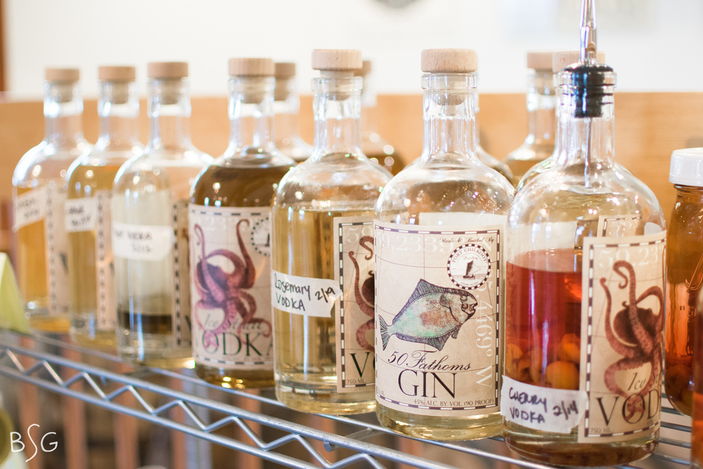 50 Fathoms Gin and Icy Strait Vodka sit on the shelf of the tasting room, infused with fruits and hints of other flavors awaiting for their opportunity to be used in a cocktail.