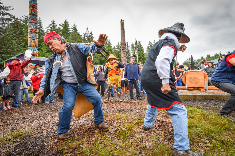 Carvers Terry Peele and Clarence Peele dance before the poles are raised in Hydaburg. The raven pole was designed by Jerry Peele. Other carvers on the project included Sonny Peele and TJ Young