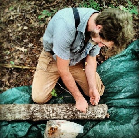 Derick inoculating a log with shiitake spawn.