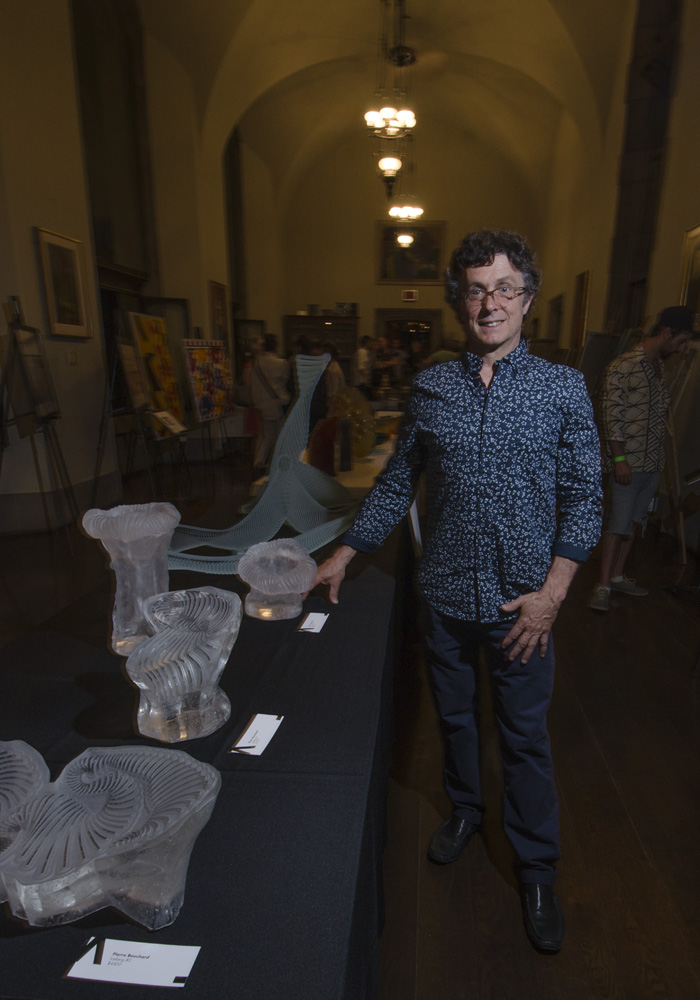 Pierre Bouchard standing with some of hisglass sculptures