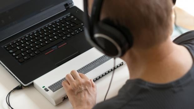 Blind person using braille keyboard attached to laptop