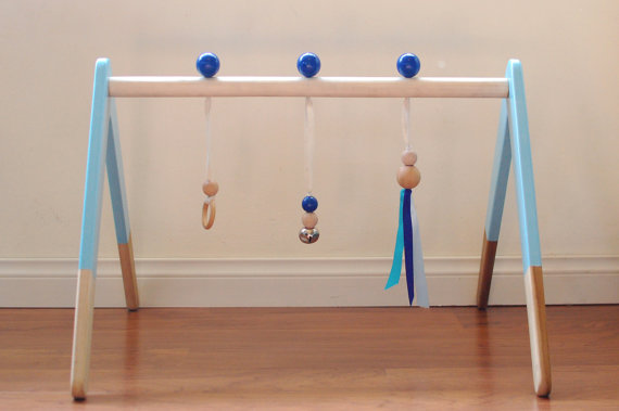 Baby Gyms - Something simple and sturdy allows for the focus to remain on the toy hanging from it. Bells, teething rings, and chimes also make wonderful baby gym toys! Baby will also need a soft place to lay, so a  blanket ,  mat , or  sheepskin  would be a nice accompaniment.