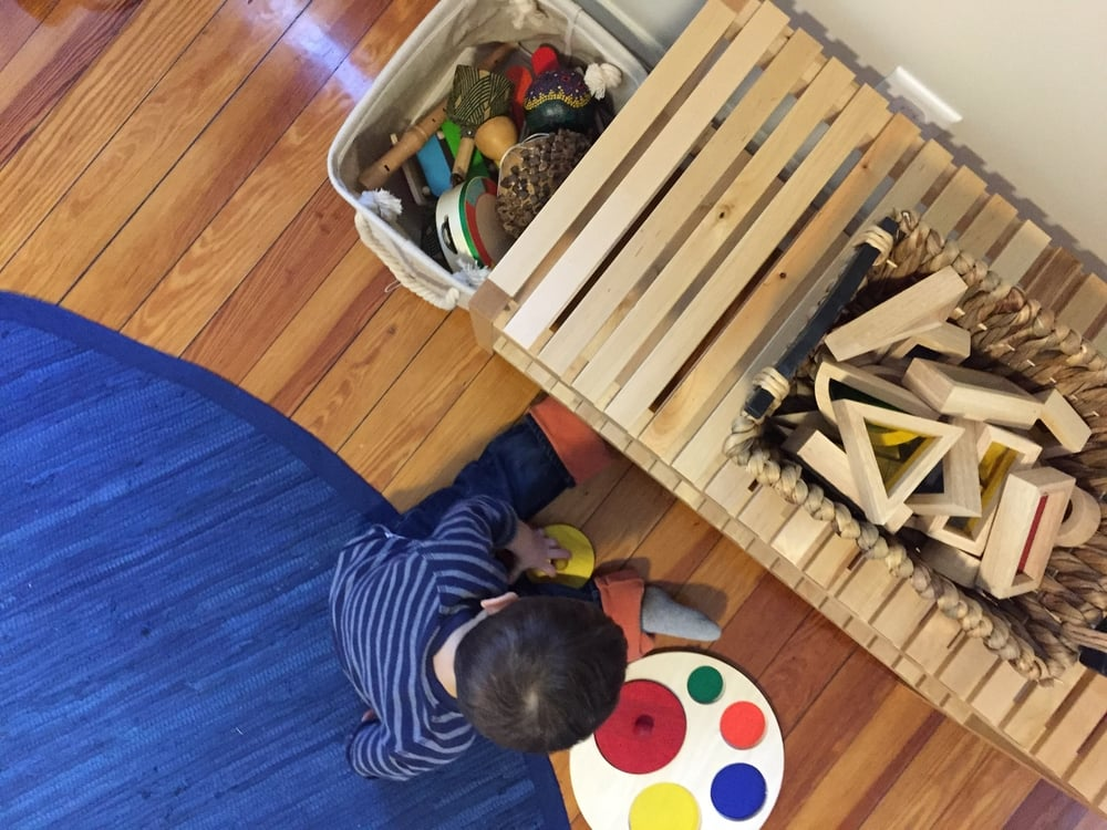 A basket of instruments, some colored see-through blocks, and a circle puzzle are holding down the fort in W's room.
