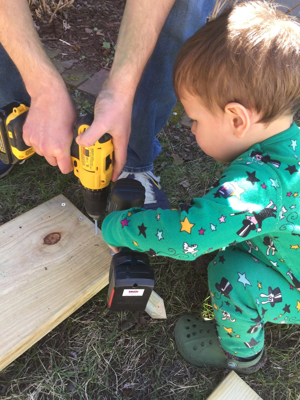Using his pretend drill to help build a sandbox