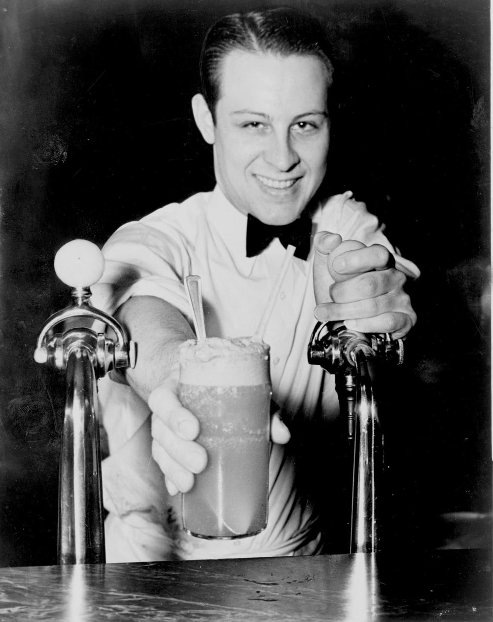 A Boston Cooler or Vernor's Float, being served with a smile by Eddie Skinks of Detroit's little known corrupt soda fountain gang. Not tipping Eddie proved to be a mistake.