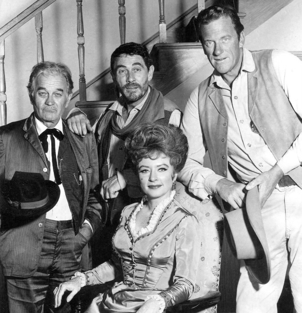 The cast of Gunsmoke, 1967. They agreed to sit for this photo only after everyone agreed to have both hands where the others could see them. Doc, ever the rebel and pocket pool player, kept one hand in his pocket and the other under his hat. He was severely reprimanded and subsequently written out of a love scene with Kitty as punishment. He died a broken man and was buried with his hands in his pockets.