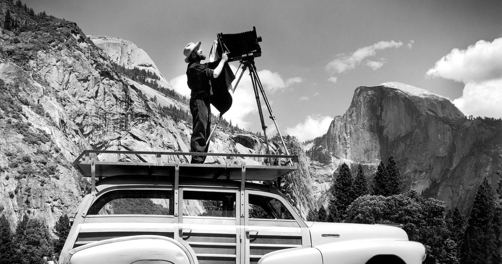 """Ansel Adams and his famous box camera in Yosemite. Adams is also credited with developing the first Google mapping vehicle. Unfortunately he fell off approximately every half mile or so and the whole endeavor was scrapped. """"Worst idea ever,"""" said Adams."""
