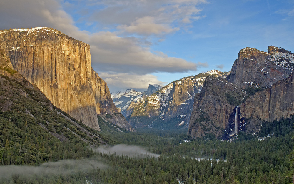 A tunnel view of Yosemite Valley, with Half Dome in the distance. The waterfall on the right is over 2,500 feet tall. The fog along the bottom of the valley was created by the National Park Service for ambiance.